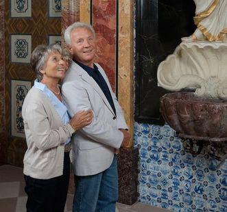 Besucherpaar betrachtet eine Statue in Schloss Favorite Rastatt